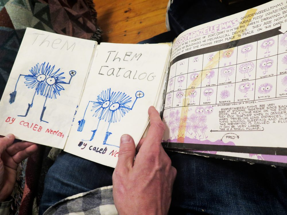 "Neelon holds Emberley's ""Big Purple Drawing Book"" next to a drawing he made from it when he was a kid. (Andrea Shea/WBUR)"