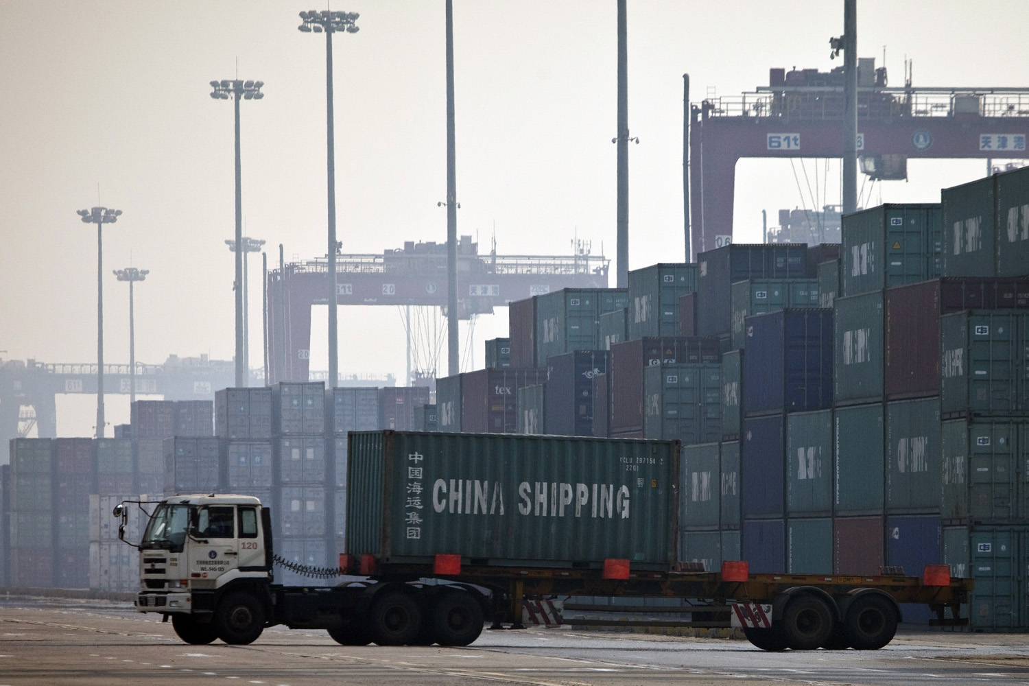 In this photo taken Tuesday, Feb. 28, 2012, a truck transports a container to be loaded onto a ship at a port in Tianjin, China. (Alexander F. Yuan/AP)
