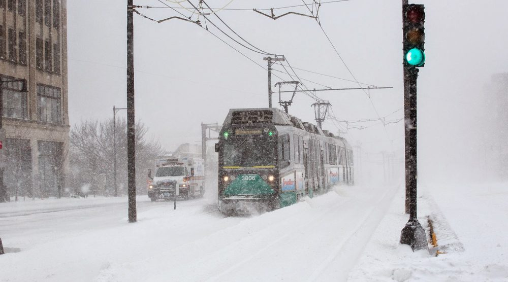Emerging from a snowstorm, a Green Line train runs along Commonwealth Avenue. (Robin Lubbock/WBUR)