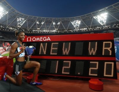 Harrison poses with the clock showing her new world record time of 12.20. (Adrian Dennis/AFP/Getty Images)