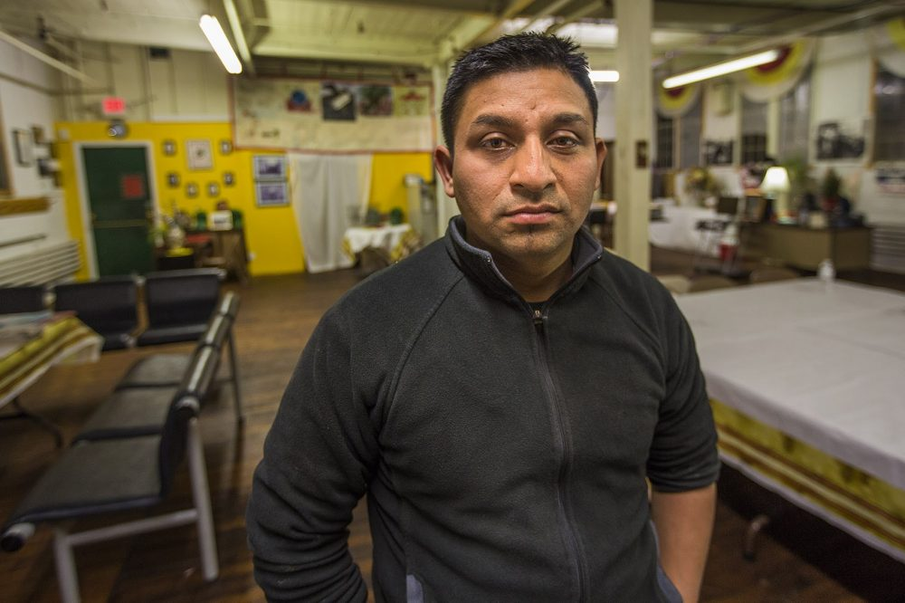 Worker Henry Aguilar placed some tile into a bag for testing. Analysis showed that the tile contained asbestos at levels requiring workers to wear specialized breathing masks to filter out cancer-causing asbestos dust. Here, Aguilar poses for a portrait at the offices of Fuerza Laboral in Central Falls, R.I. (Jesse Costa/WBUR)