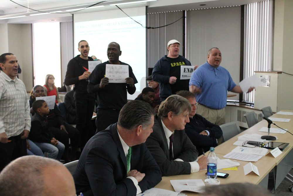 "Calvin Feliciano (far right), deputy political director for SEIU 509, interrupted Wednesday's meeting of a criminal justice working group to express the need for sentencing reforms and led protesters in a ""jobs, not jails"" chant. (Antonio Caban/SHNS)"