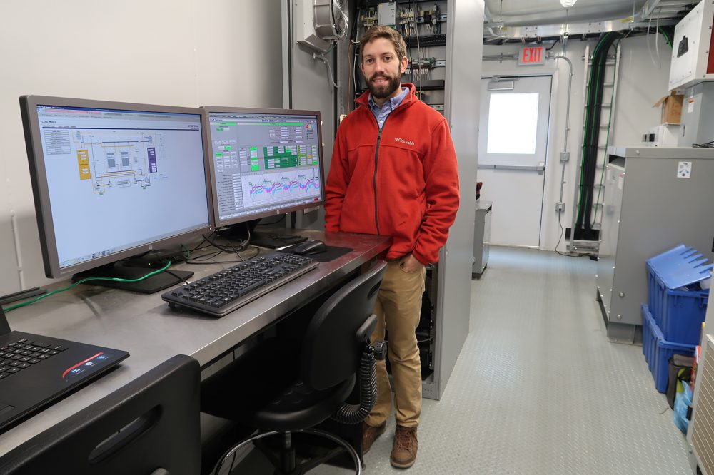Vionx Energy field engineer Michael McNeely stands in the engineering house where the monitoring of the vanadium redox flow battery occurs. (Bruce Gellerman/WBUR)