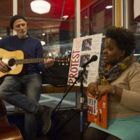 Tanya Nixon-Silberg, storyteller and co-founder of Wee The People, reads stories with Jeffrey Benson providing background music, during a ResistARTS performance in early January. (Joe Difazio for WBUR.)