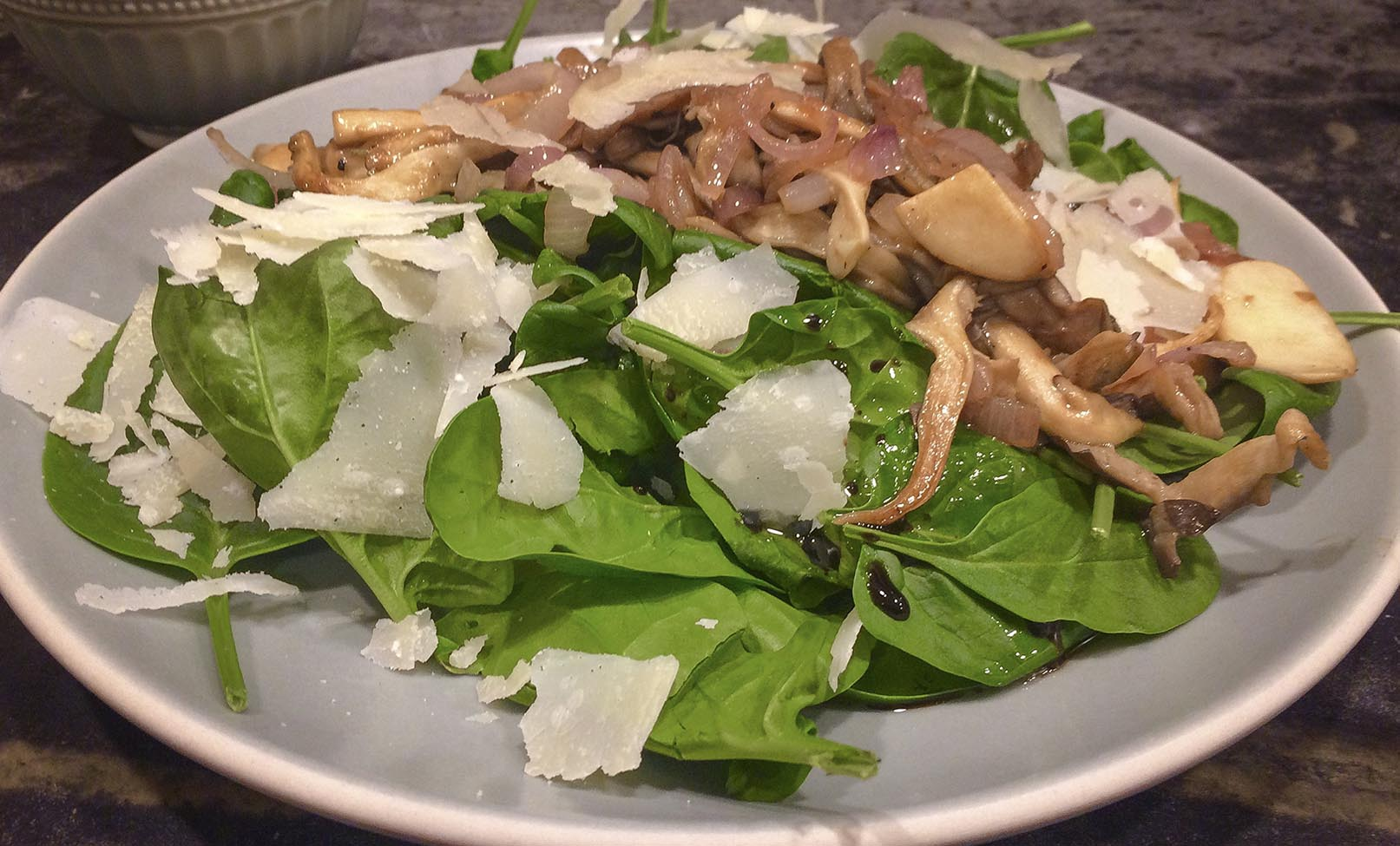 Kathy's sauteed mushrooms over baby spinach with warm garlic vinaigrette and Parmesan shavings. (Kathy Gunst for Here & Now)