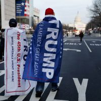 Supporters of President-elect Donald Trump walk along Pennsylvania Avenue Thursday after it was closed down to thru-traffic as security tightens ahead of the presidential inauguration. (John Minchillo/AP)