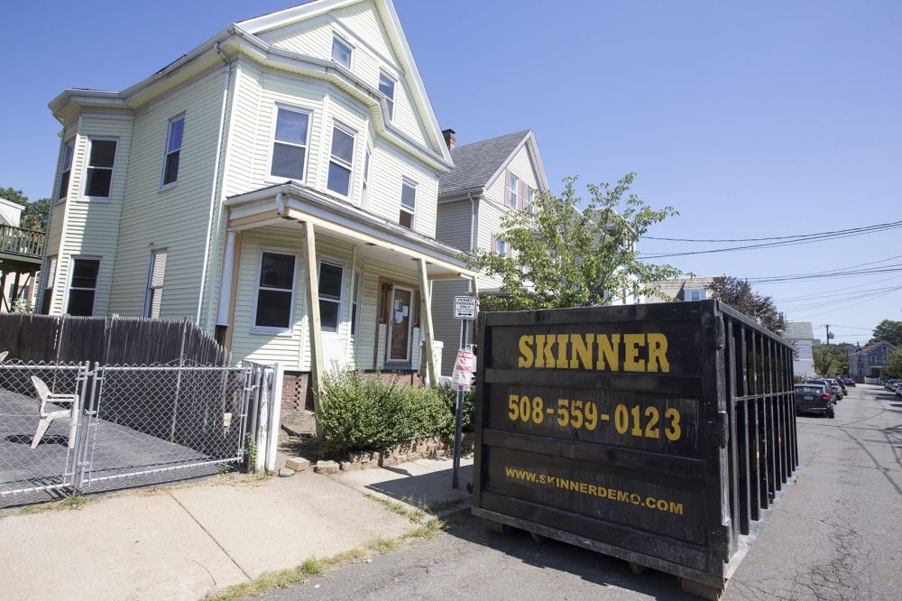 A Skinner Demolition dumpster is parked in front of a project in Somerville. (Joe Difazio for WBUR)