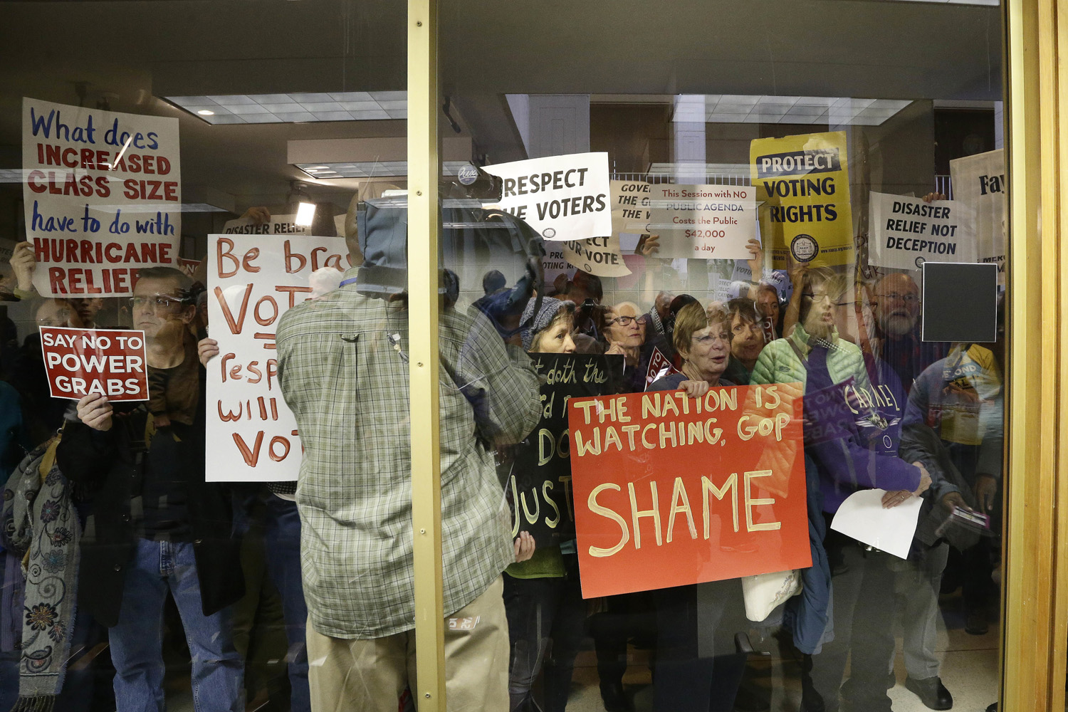 Protestors gather outside of a press conference room during a special session at the North Carolina Legislature in Raleigh, N.C., Thursday, Dec. 15, 2016. (Gerry Broome/AP)