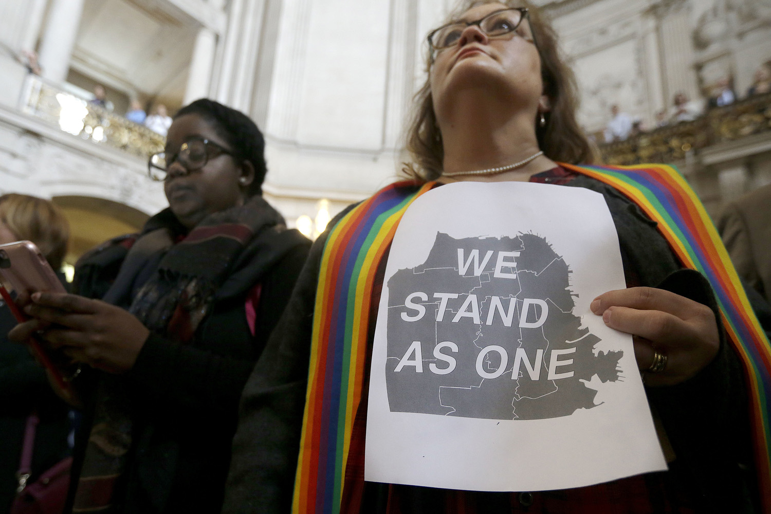 In this file photo, The Rev. Annie Steinberg-Behrman, right, provisional pastor with Metropolitan Community Church, holds a sign while listening to speakers at a meeting at City Hall in San Francisco by city leaders and community activists to reaffirm the city's commitment to being a sanctuary city. (Jeff Chiu/AP)
