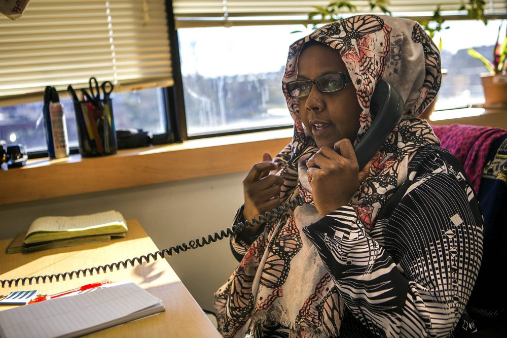 Kaftun Ahmed is a Somali interpreter and community health worker at Massachusetts General Hospital in Chelsea. Here she speaks to an immigrant patient to make sure they have received clearance for dental care. (Jesse Costa/WBUR)