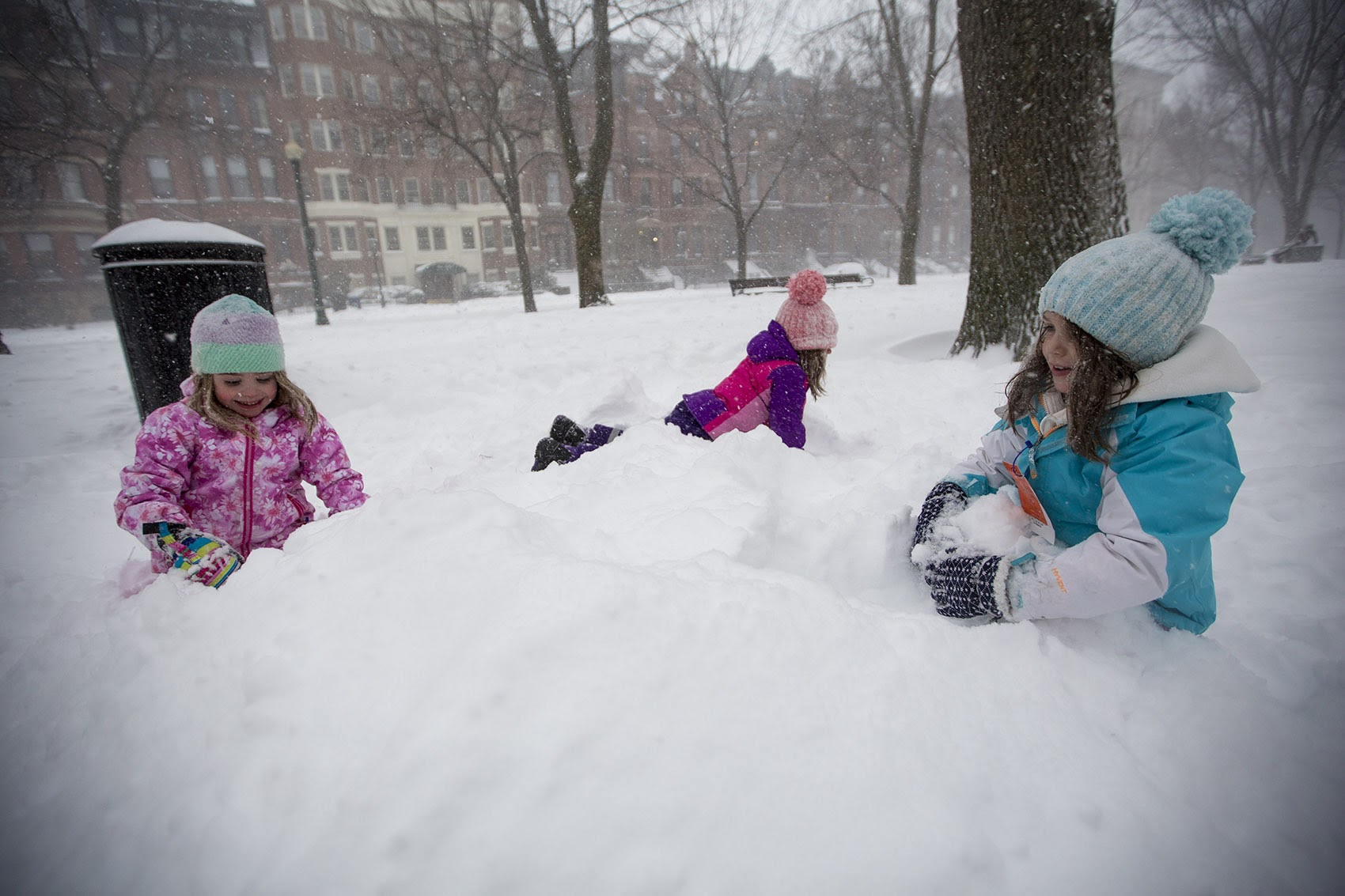 Natalie (pink), Sami (purple) and Maddie (blue) Brown play in the snow on the Commonwealth Avenue Mall. (Jesse Costa/WBUR)