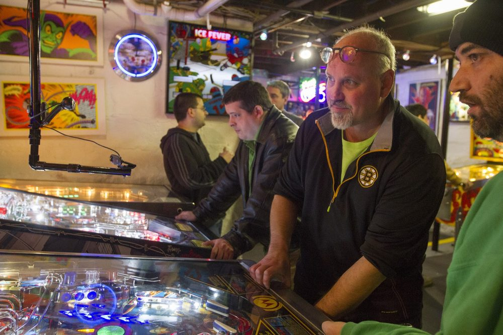 Chuck Webster (with the Bruins shirt) runs The Wicked Pissa Pinball Pit out of his home in Wakefield. (Joe Difazio for WBUR)