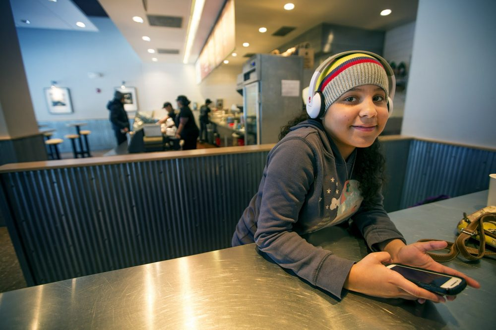 During her day off from school, Xiomary Gonzalez, 10, plays White Tiles 4 on her phone to pass the time while her mother, Xiomara Gonzalez, works at the register at Chipotle. (Jesse Costa/WBUR)