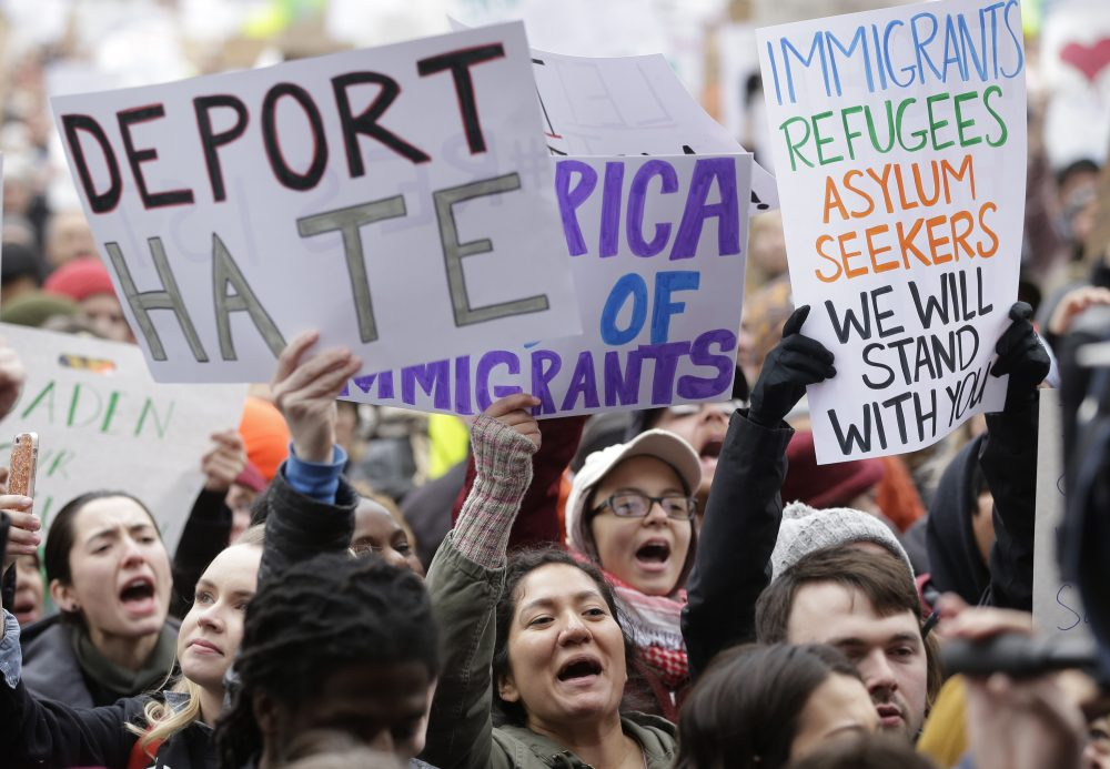 By targeting immigrants, the administration puts our global universities, hospitals, scientific research centers and start-ups at risk. Pictured: Demonstrators display placards in Boston, Sunday, Jan. 29, 2017, during a rally against President Donald Trump's order that restricted travel to the U.S. (Steven Senne/AP)