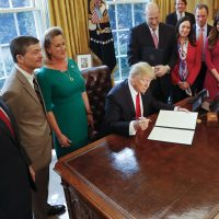 President Donald Trump prepares to sign an executive order that will direct the Treasury secretary to review the 2010 Dodd-Frank financial oversight law. (Pablo Martinez Monsivais/AP)