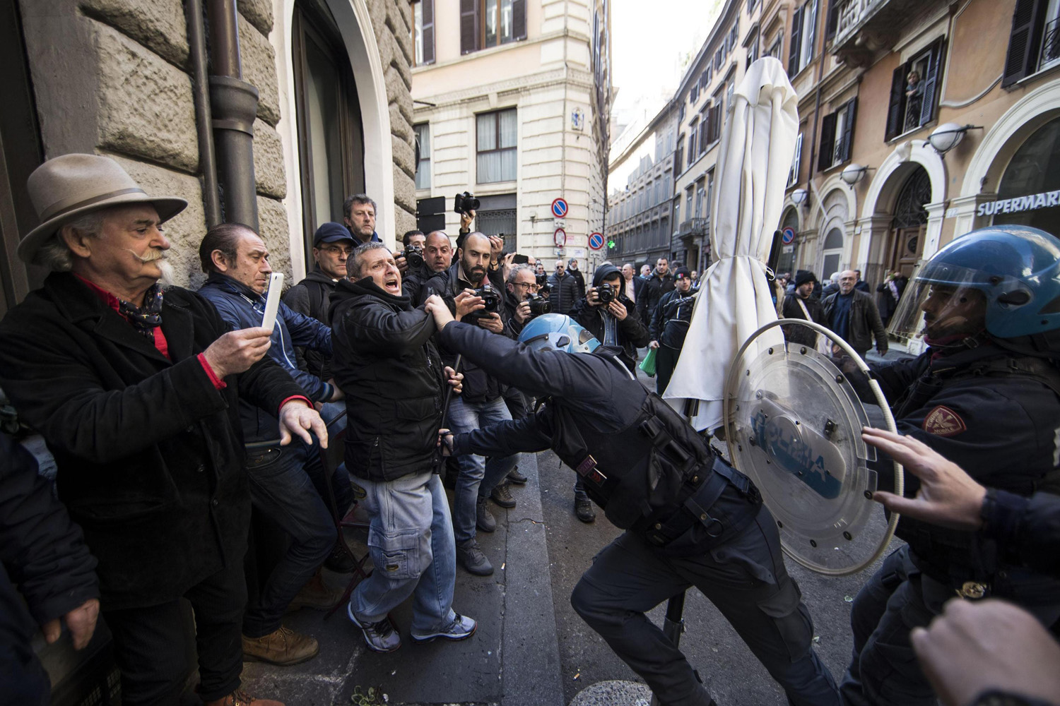 Riot police clash with taxi drivers and street sellers during a demonstration, in Rome, (Massimo Percossi/AP)