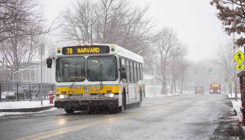 A bus made its way down a lonely Concord Avenue as snow began to fall at the start of Tuesday's storm. (Robin Lubbock/WBUR)