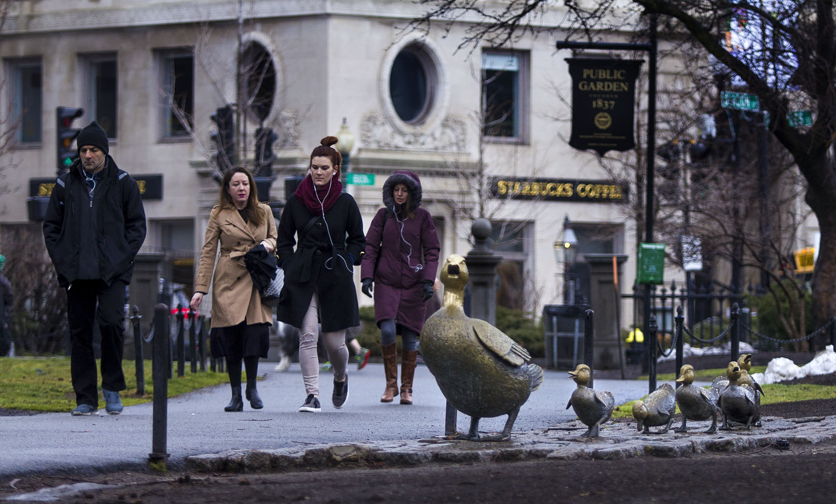 "Pedestrians walking by the ""Ducklings"" in the Public Garden in Boston. (Jesse Costa/WBUR)"