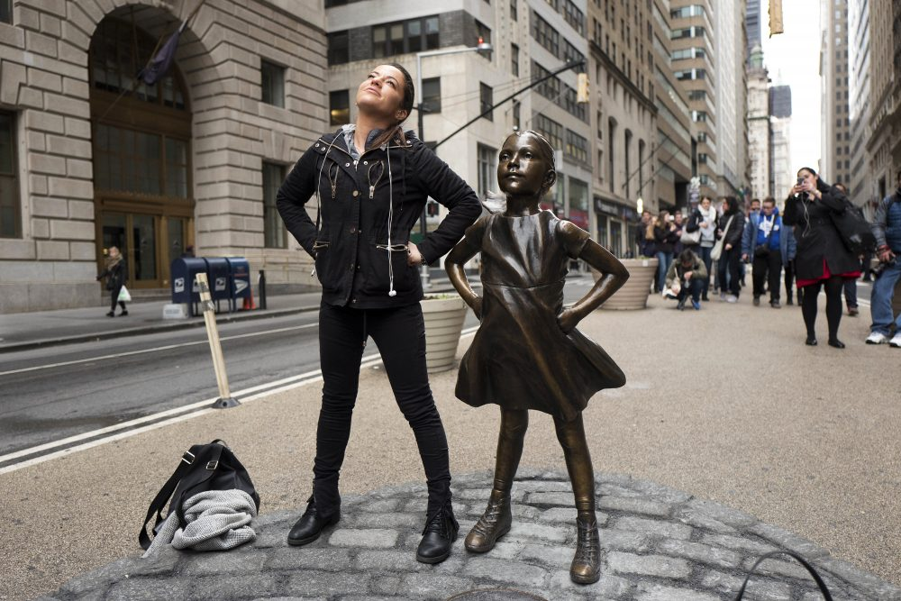 "A woman strikes a pose with the ""Fearless Girl"" statue on Wednesday, International Women's Day. (Mark Lennihan/AP)"
