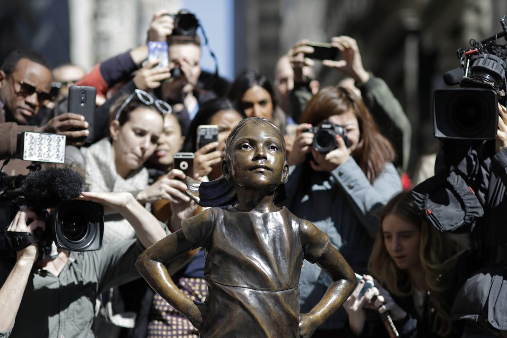 People flock to the new statue on Wall Street to take photos. (Mark Lennihan/AP)