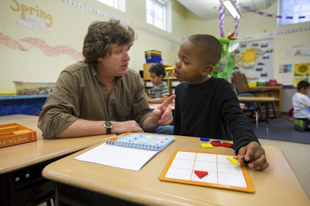 Lawrence Elementary first grade teacher Jonathan Norwood guides Shamar Morris on how to play the geometric puzzle game Meta-Forms. (Jesse Costa/WBUR)