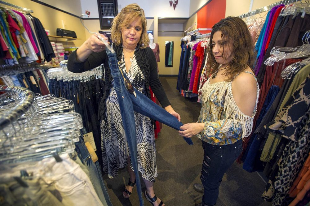 Fatima Ortiz, left, shows Gloria Rivas a pair of jeans at her clothing shop, Amazonia, on Broadway in Chelsea. (Jesse Costa/WBUR)