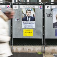 A man walks past electoral posters displaying the presidential candidates, Benoit Hamon, left, Emmanuel Macron, center, and Marine Le Pen in Paris, France. (Kamil Zihnioglu/AP)