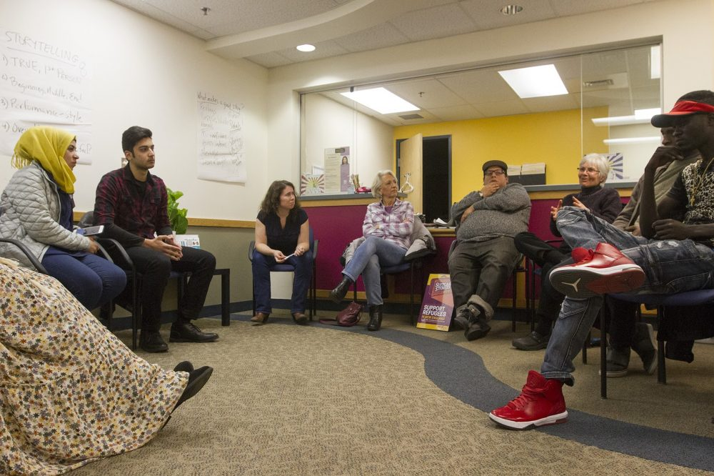 "The organizer behind the International Institute of New England and Massmouth's live storytelling collaboration ""Suitcase Stories"" sees it as a way to break down cultural barriers and turn strangers into neighbors. Here, a group of potential storytellers gather at the International Institute's Lowell office for a storytelling workshop. (Joe Difazio for WBUR)"