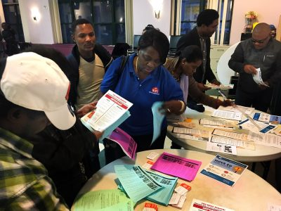 Attendees at a community forum collect handouts with information on immigration services. Many members of Boston's Haitian community have been worried about the fate of their Temporary Protected Status which enables them to live and work in the U.S. The Trump administration announced Monday Haitians' TPS status would end. (Shannon Dooling/WBUR)