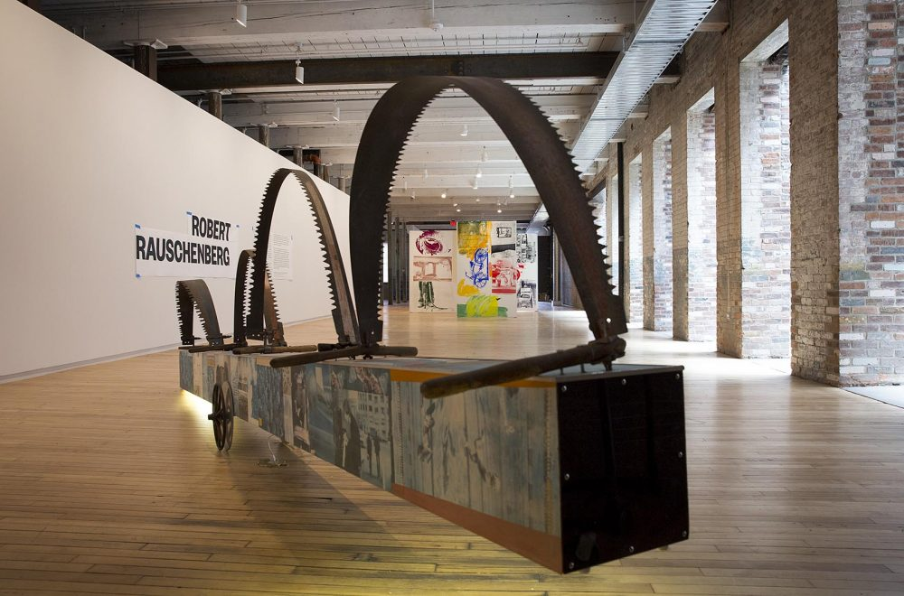 """Robert Rauschenberg's """"A Quake in Paradise (Labyrinth)"""" seen through the jaws of his work, """"The Lurid Attack of the Monsters from the Postal News Aug 1875,"""" ahead of the building's opening. (Robin Lubbock/WBUR)"""