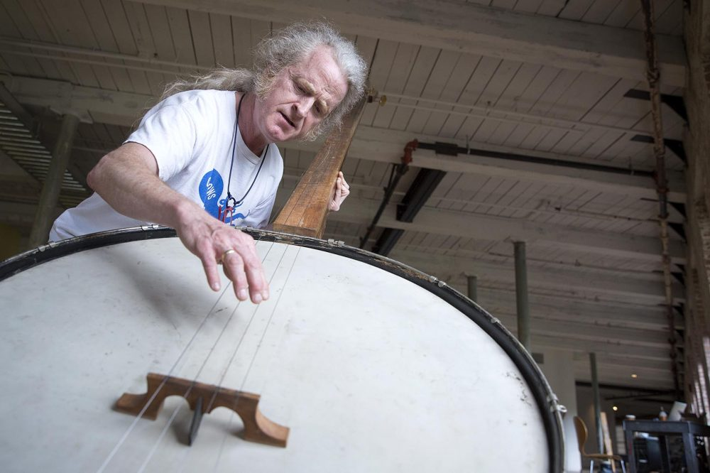 Musician Mark Stewart plays a 9-foot banjo created by Gunnar Schonbeck. (Robin Lubbock/WBUR)