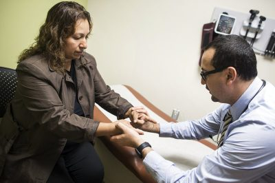Dr. Cesar Barba (right), a family physician at the UMMA Community Clinic's Fremont Wellness Center in South Los Angeles, treats Lourdes Flores Valdez, 42, for her diabetes and other health issues. (Maya Sugarman/KPCC)