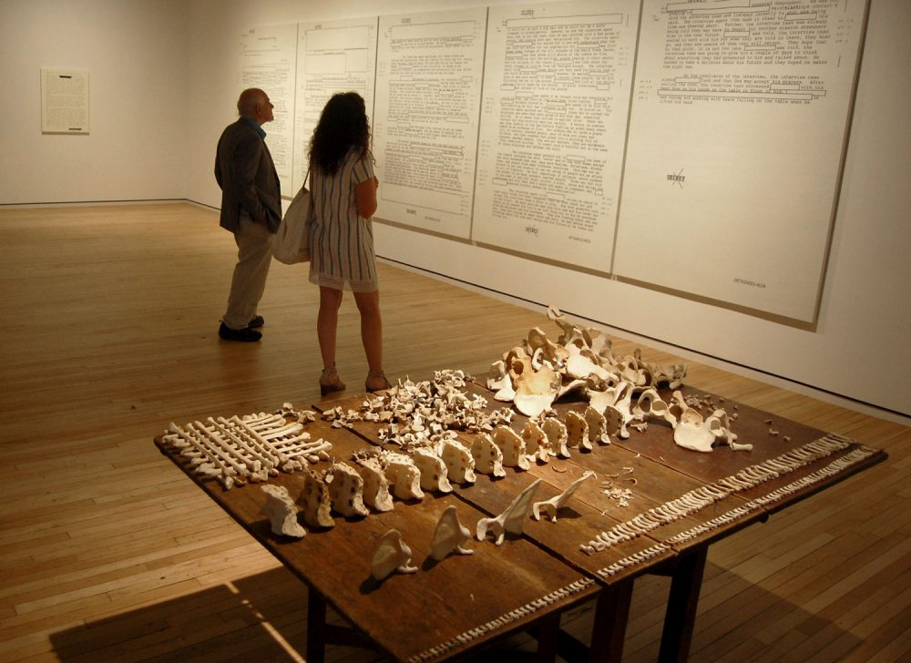 Jenny Holzer's installation at MASS MoCA includes tables of actual human bones and screenprints of declassified American military documents recording prisoner abuse. (Greg Cook/WBUR)