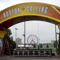 Construction of the entrance to Boston Calling is almost complete on a wet Thursday afternoon. The ferris wheel awaits the arrival of the crowds on Friday. (Robin Lubbock/WBUR)