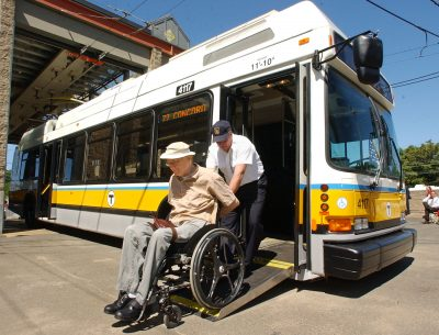 Jack Callinan, an instructor for MBTA bus operations, pushes Larry Braman of Cambridge, Mass., out of a low-floor, fully automated electric trolley bus after a news conference announcing the introduction of the new trolley buses Friday, June 4, 2004 at the MBTA's carhouse in Cambridge, Mass. The wheelchair accessible vehicles have modern accomodations such as air conditioning, automatic stop announcements and onboard visual displays depicting each stop. (AP Photo/Lisa Poole)