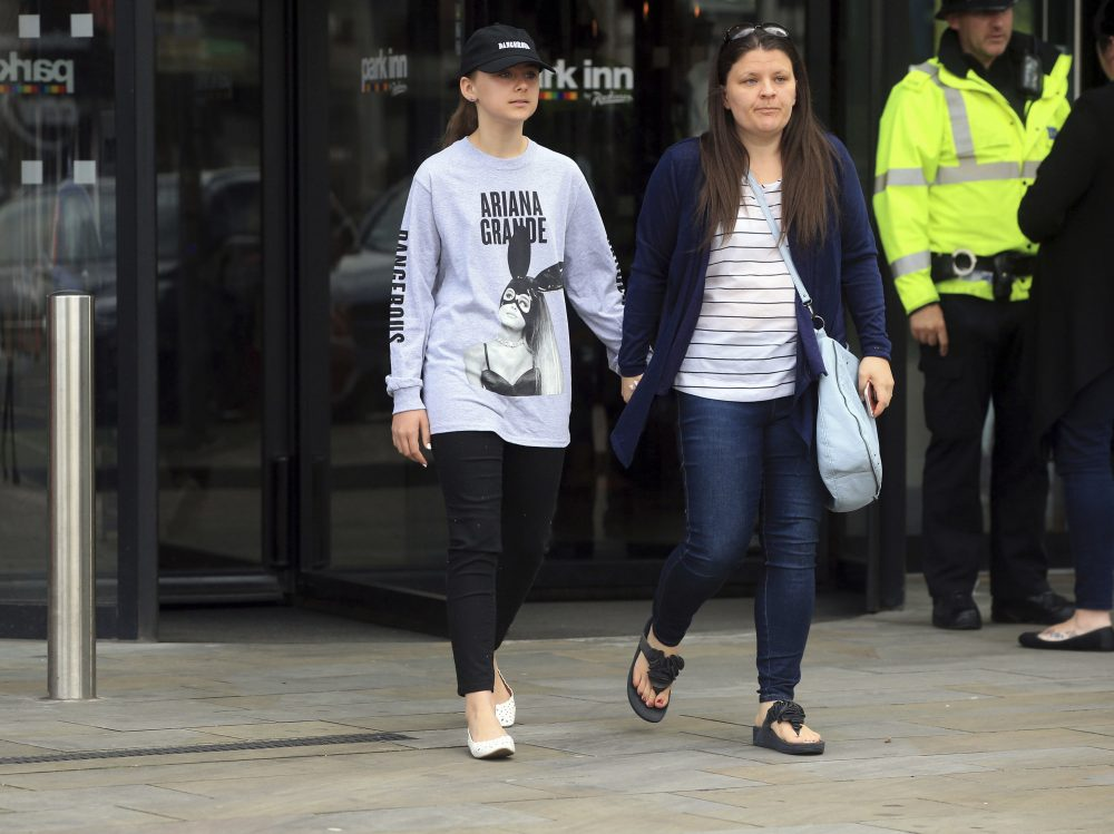 Mother Amy Trippitt and her daughter Grace, who attended the concert in Manchester, Britain, Tuesday May 23, 2017, a day after an explosion. An apparent suicide bomber set off an improvised explosive device that killed over a dozen people at the end of an Ariana Grande concert, Manchester police said Tuesday. (Danny Lawson/PA via AP)