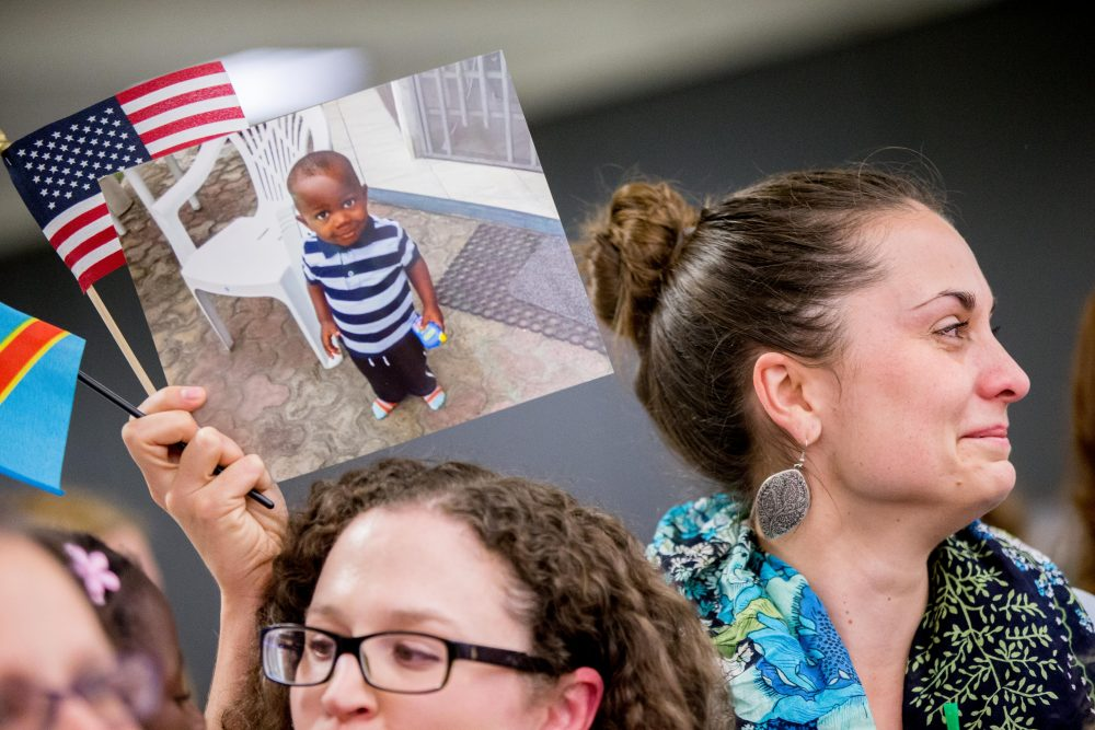 If inter-country adoptees deserve to feel secure in the nation they call home, writes Margaret Homans, so do all the other immigrants who are part of our national family. Pictured: Sarah from Philadelphia holds up a photograph of Gedeon, 3, as a group of families waiting for long-stalled exit permits for adopted children from the Congo gathered for a welcome celebration at Dulles International Airport on Wednesday, Nov. 11, 2015. (Andrew Harnik/AP)