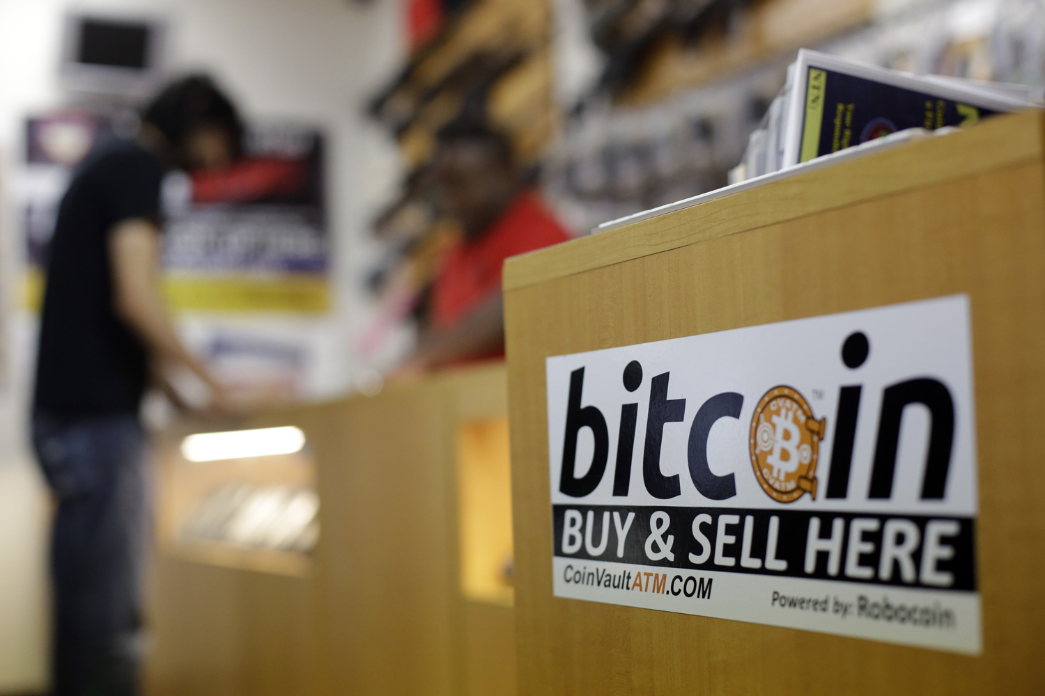 In this Wednesday, Aug. 20, 2014 photo, Jon Rumion, background left, talks with Michael Cargill at Central Texas Gun Works, in Austin, Texas. Rumion purchased two guns at the store using bitcoin. (AP Photo/Eric Gay)