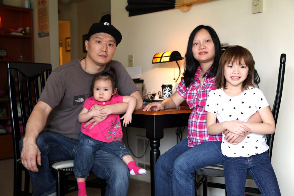 Korean adoptee Adam Crapser poses with his daughters and his wife, Anh Nguyen, in the family's living room in Vancouver, Wash. on March 19, 2015. (Gosia Wozniacka/AP)