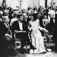 President John F. Kennedy and his wife Jacqueline, look on as poet Robert Frost, right, takes his seat in the East Room of the White House on April 30, 1962. (AP)