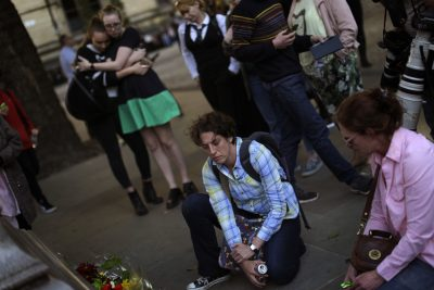 After two days of studying the faces of the individuals killed in the Manchester bombing, writes Julie Wittes Schlack, I feel compelled to also peer into the face of the man who blew himself to bits. Pictured: People stand next to flowers after a vigil in Albert Square, Manchester, England, Tuesday May 23, 2017, the day after the suicide attack at an Ariana Grande concert that left 22 people dead. (Emilio Morenatti/AP)
