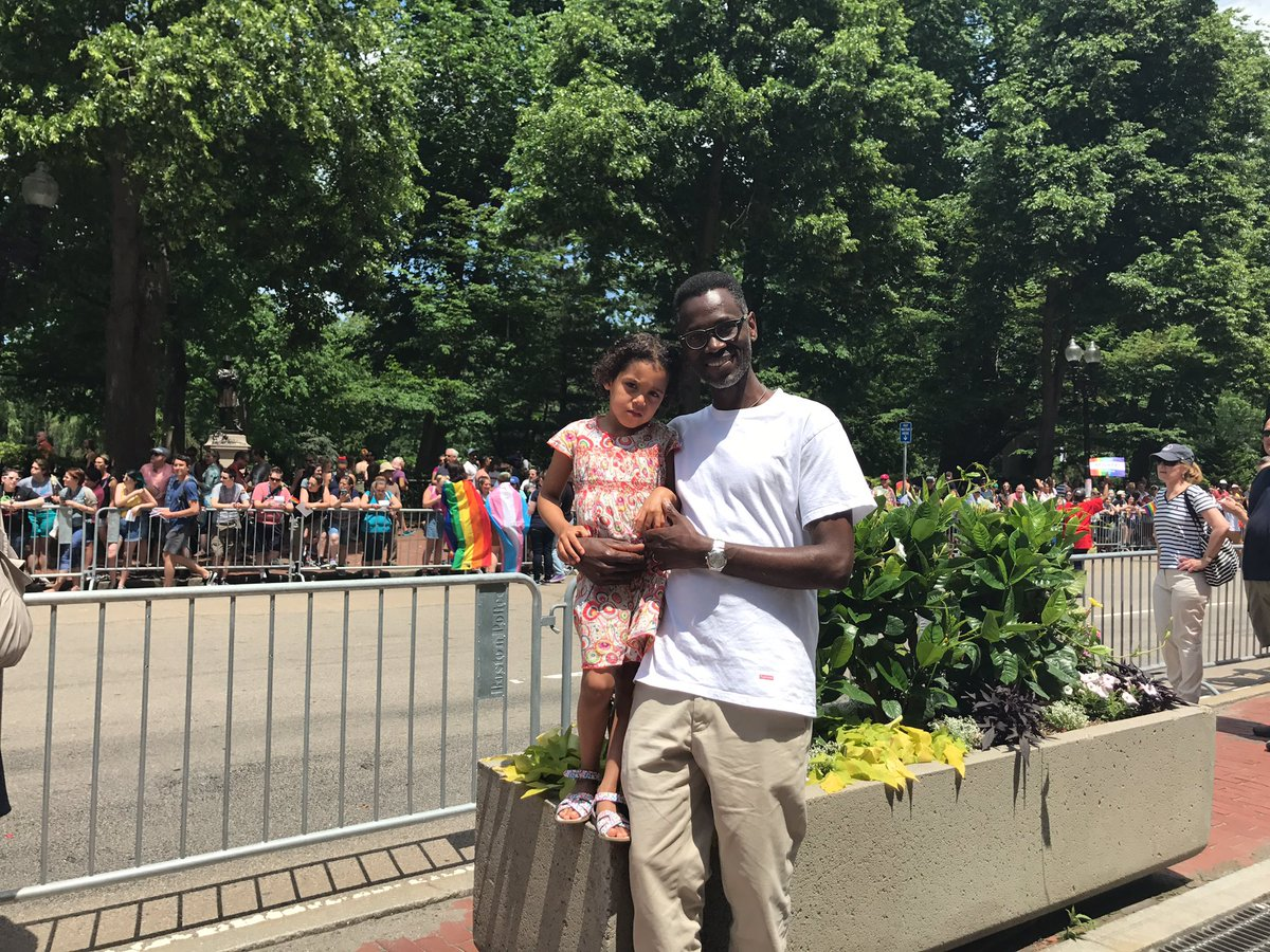 Kenya-native Maina Muthee with his daughter Abigail at the Pride Day Parade in Boston on Saturday. (Kassandra Sundt/WBUR)