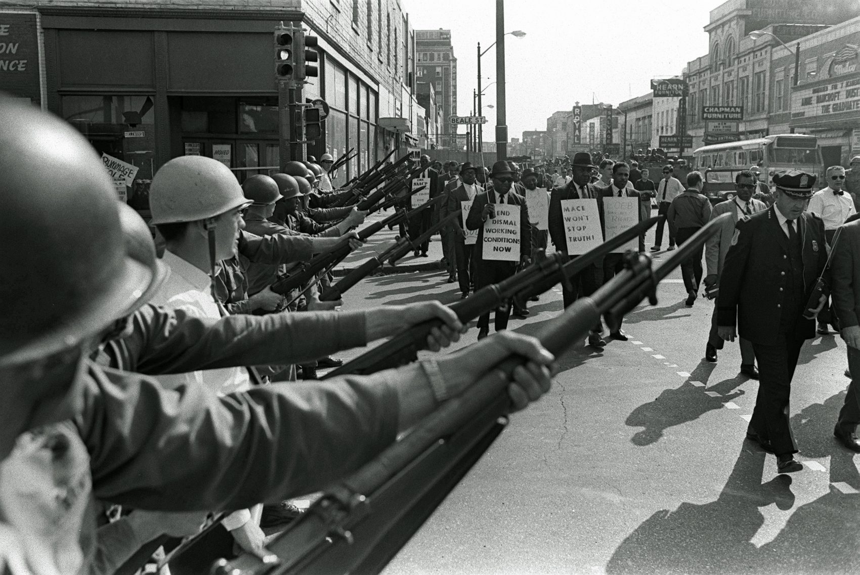 Striking Memphis sanitation workers march past Tennessee National Guard troops with fixed bayonets during a 20-block march to City Hall, March 29, 1968, one day after a similar march erupted in violence, leaving one person dead and several injured. (Charlie Kelly/AP)