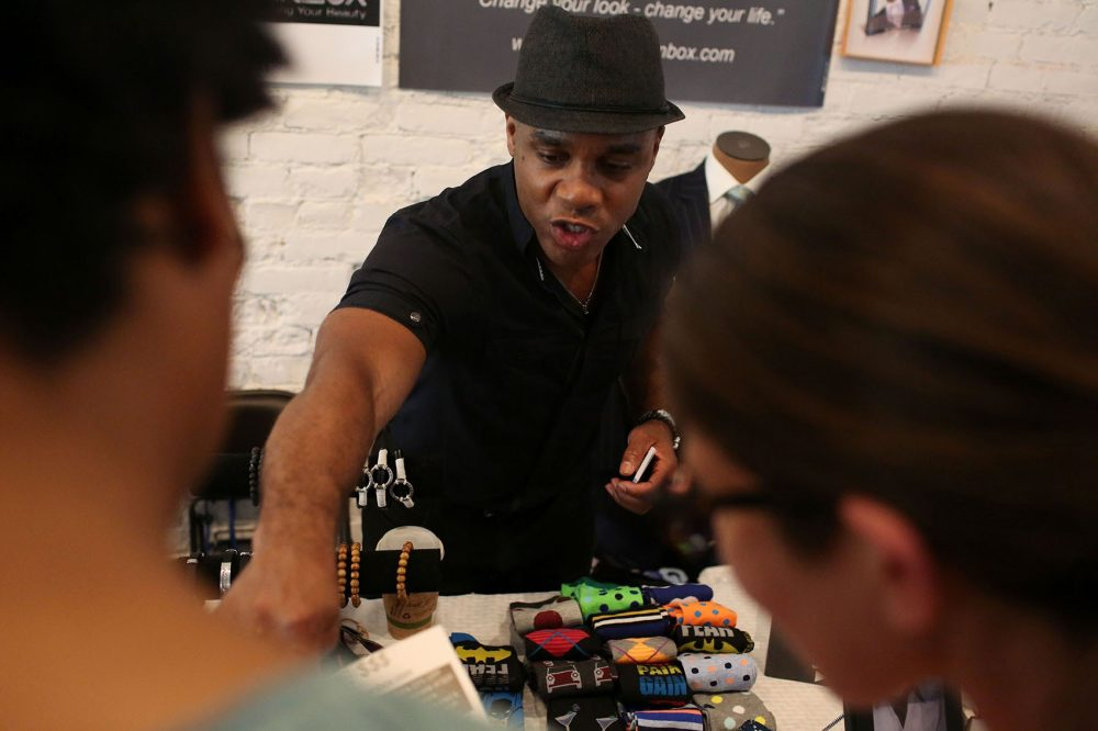 Lance McBrayer talks to shoppers at his retail space at Black Market. (Hadley Green for WBUR)