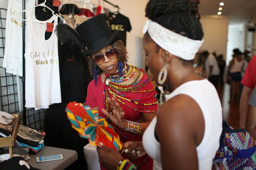 Shalair Armstrong, owner of the retail store Diaspora Africa, speaks to a customer at the Black Market in Dudley Square. (Hadley Green for WBUR)
