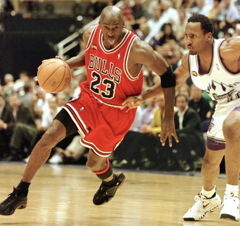 Michael Jordan of the Chicago Bulls sticks his tongue out and drives past  Shandon Anderson of 3add64ad0