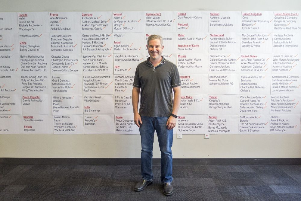 Invaluable CEO Rob Weisberg stands in front of a wall at his office showing the geographic reach of auction houses that have singed on to the e-commerce site. (Andrea Shea/WBUR)