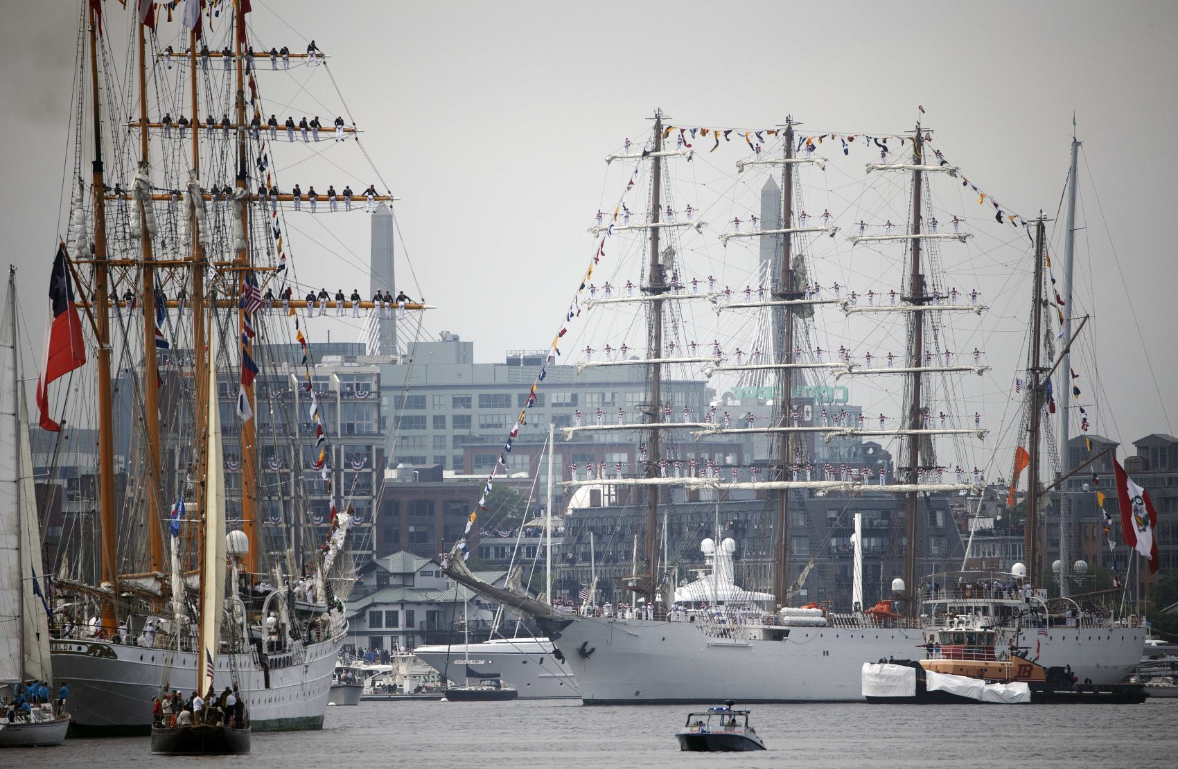 The Peruvian Navy tall ship Union, center, turns around in the inner harbor in front of the Chilean Navy tall ship Esmerelda, left, during Sail Boston's Parade of Sail. (Michael Dwyer/AP)