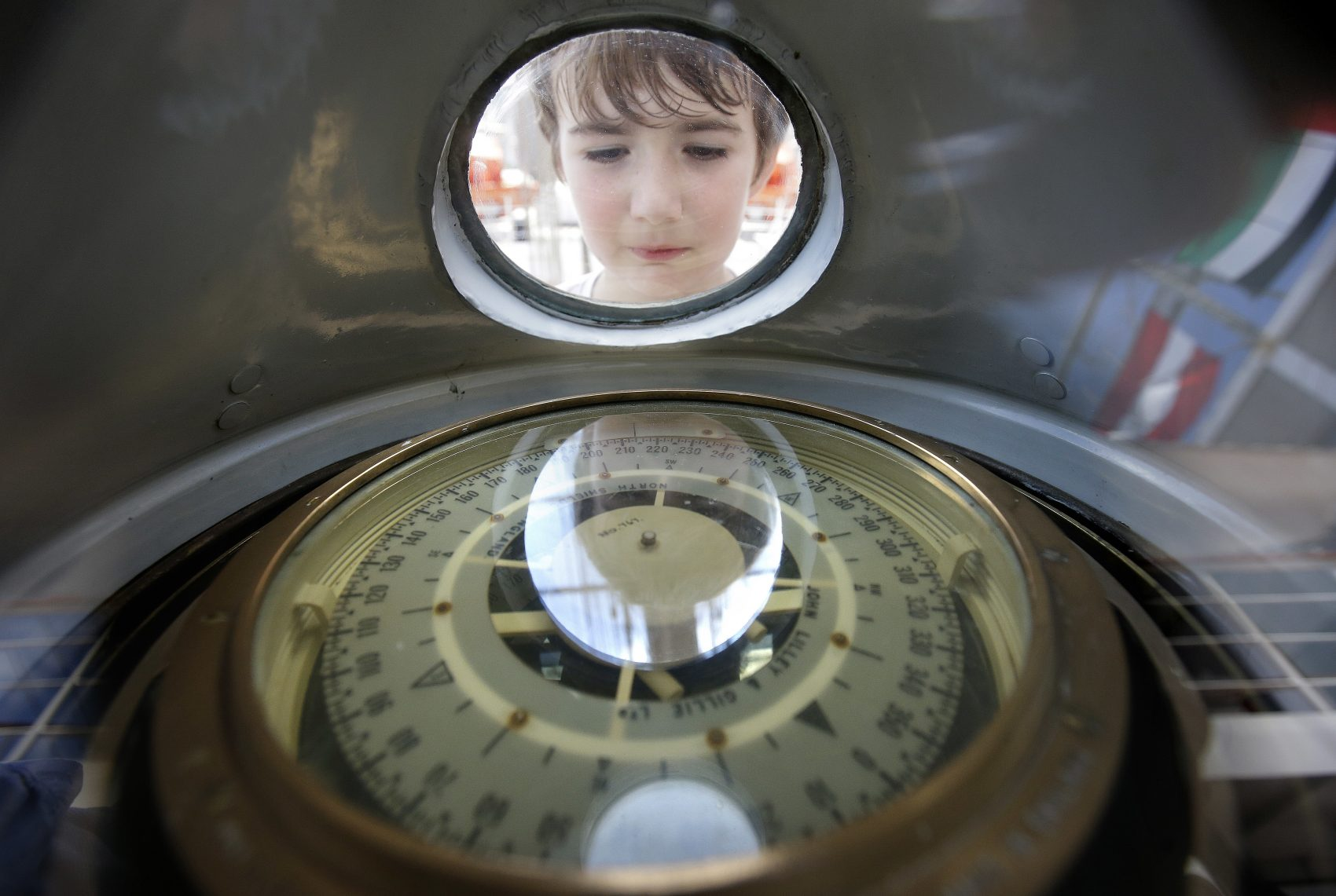 Sean Sullivan, 8, of Wellesley, Mass., examines a compass aboard the Peruvian Navy tall ship Union, which was open to the public to visitors on Sunday. (Steven Senne/AP)