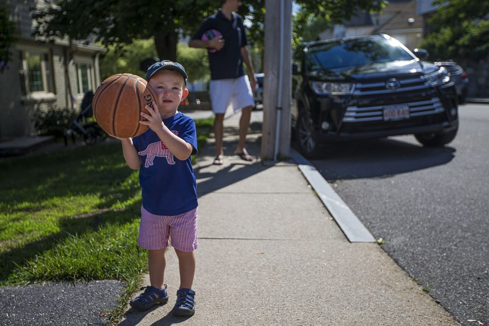 Two-and-a-half-year-old Robbie Klein has hemophelia, a medical condition in which the ability of the blood to clot is reduced. Here Robbie prepares to shoot some hoops with his father, Joel. (Jesse Costa/WBUR)